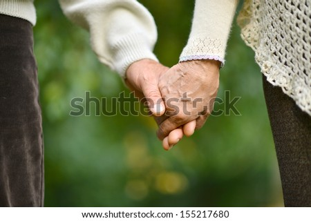 Hands held together on a natural green - stock photo