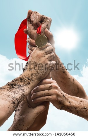 hands held together to win a medal, team work - stock photo