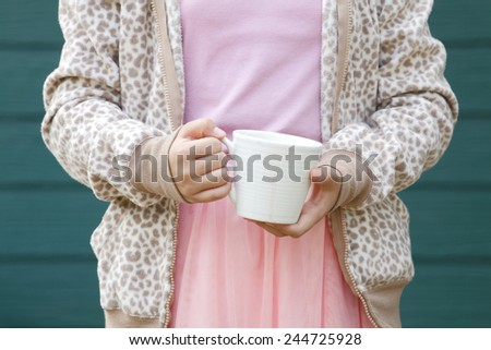 Hands hold a cup