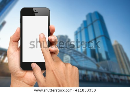 Hands hold and touch blank screen smart phone with office building background - stock photo