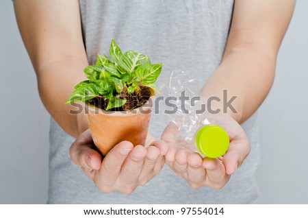 Hands hold recycle bottle and green plant, horizontal - stock photo