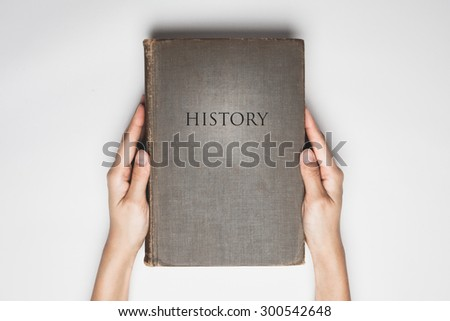 "hands hold the  book with a word of "" History "" on cover - stock photo"