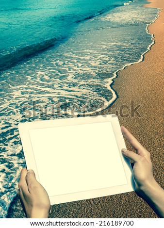hands hold the tablet at the beach - vintage style - stock photo