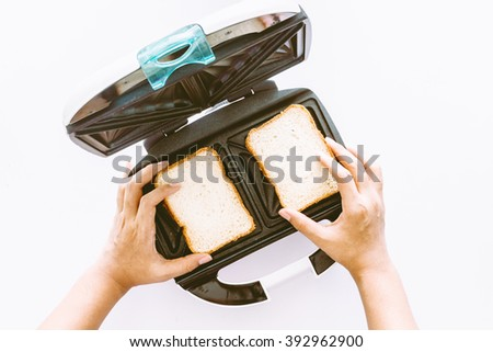 Hands hold toaster with bread slices making machine tool fast on white background - stock photo