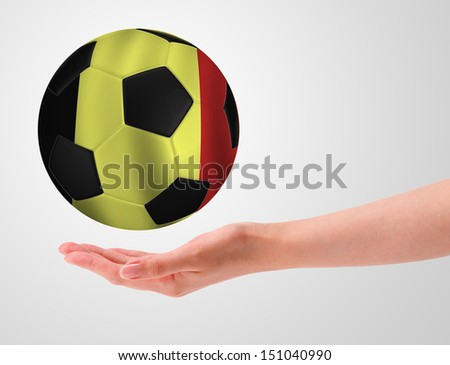 Hands holding a ball with flag of belgium - stock photo