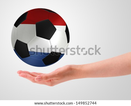 Hands holding a ball with flag of netherlands - stock photo