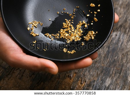 Hands holding a black plate with gold nugget grains, close-up - stock photo