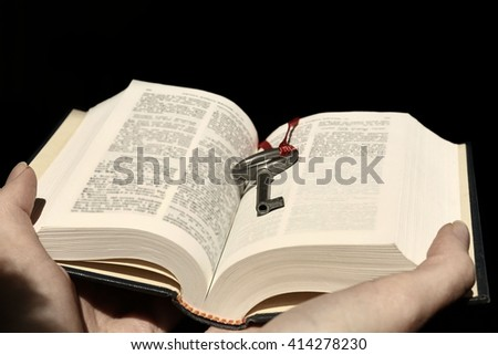 Hands holding a book with vintage key on black background. - stock photo
