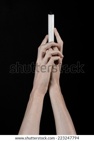 Hands holding a candle, white candle, studio, isolated, black background, praying, church, store, heat, faith, soul, religion, prayer, symbol - stock photo
