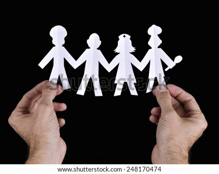 Hands holding a chain of dolls of paper, which represent the civil cooperation - stock photo