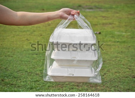 hands holding a clear plastic bags containing three foam containers - stock photo