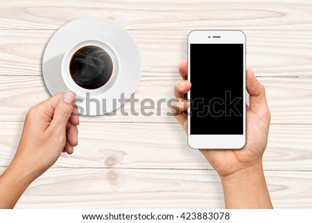 Hands holding a cup of coffee and White Smart phone on white wooden table - stock photo