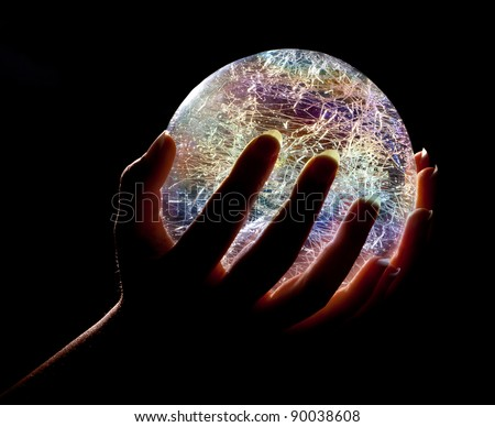 Hands holding a glowing colorfull glass or crystal ball - stock photo