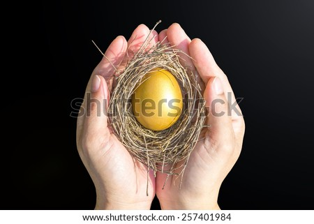 Hands holding a golden egg in a nest isolated on black background: A golden egg opportunity concept of wealth planning and a fortune to be rich - stock photo