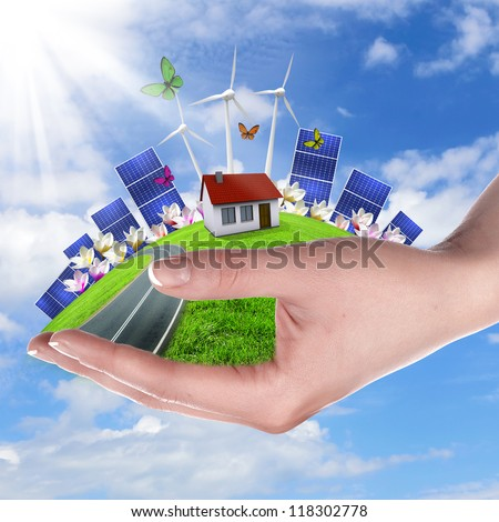 Hands holding a green earth with solar batareis - stock photo