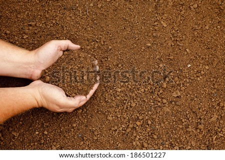 Hands holding a handful of fine rich soil