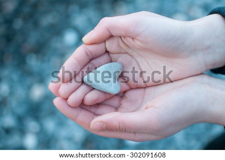 Hands holding a heart on defocused stone background - stock photo