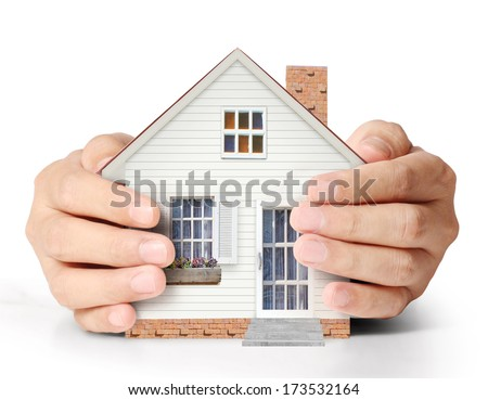 Hands holding a house - representing home ownership and the Real Estate business.  - stock photo