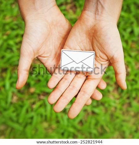 hands holding a letter symbol - stock photo