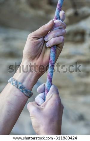 Hands holding a nylon rope climbing - stock photo