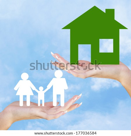 Hands holding a paper Home and Happy Family on sky blue background - stock photo