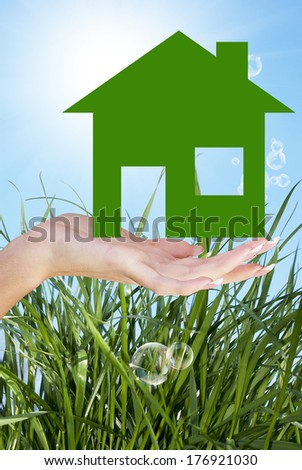 Hands holding a paper Home on grass green background
