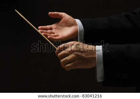 Hands holding a pointing stick isolated on dark background.
