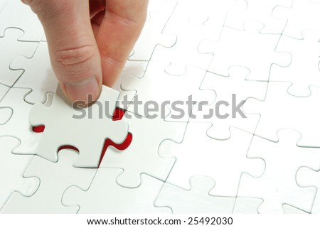 hands holding a puzzle piece - stock photo