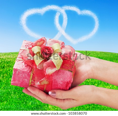 hands holding a red gifts in the sky, and two hearts - stock photo