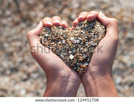 Hands holding a sand in form of the heart - stock photo