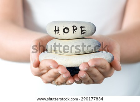 "Hands holding a small stack of pebbles with 'Hope""' written on the top stone. - stock photo"