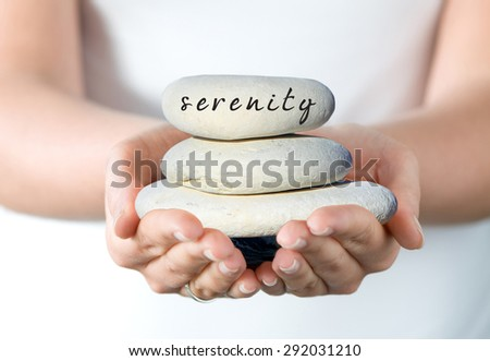 """Hands holding a small stack of pebbles with 'Serenity""""' written on the top stone. - stock photo"""