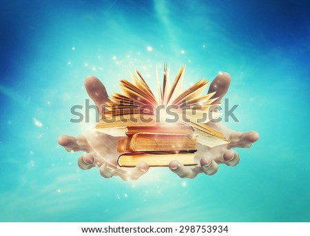 hands holding a stack of books on a sky background. Open book. with magic light - stock photo