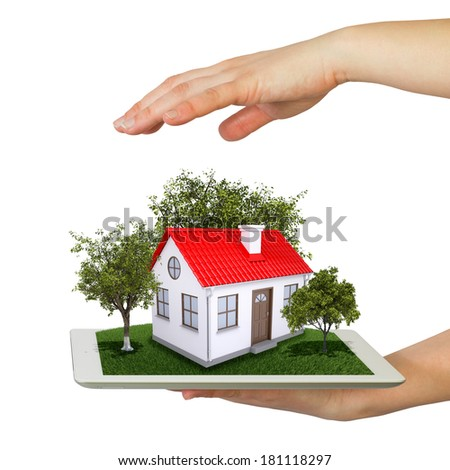 Hands holding a tablet pc and small house with land. Isolated on white background