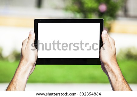 Hands holding a tablet with white screen. - stock photo