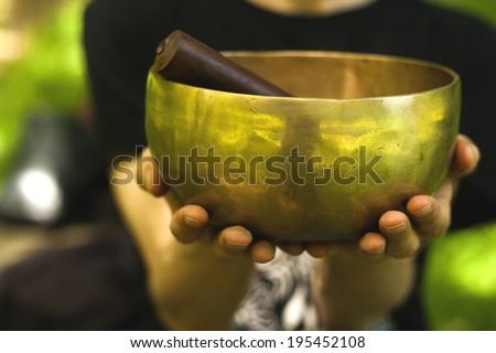 hands holding a tibetan bowl - stock photo