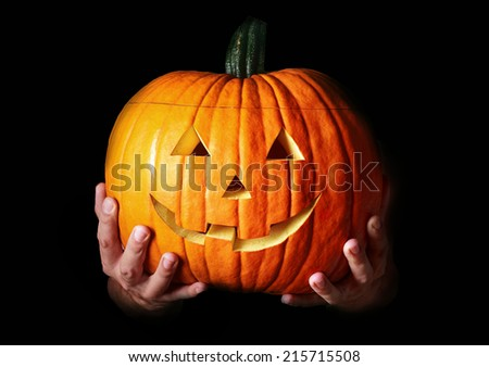 Hands holding a traditional Halloween creepy carved pumpkin, with copy space on black - stock photo
