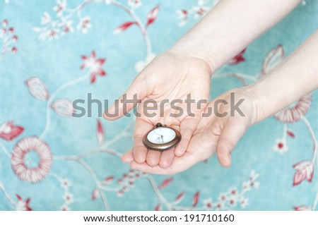 Hands holding a vintage pocket watch, on the background a floral wallpaper - stock photo