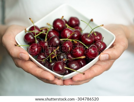 Hands holding a white bowl with ripe cherries. Shallow dof - stock photo