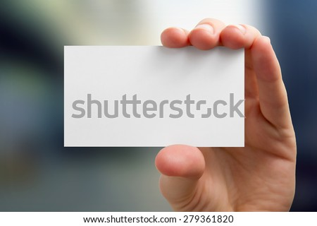 Hands holding a white business visit card, gift, ticket, pass, present close up on blurred blue background. Copy space - stock photo