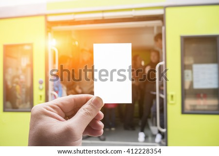 Hands holding a white business visit card, gift, ticket, pass, present close up on blurred of train station,subway,People wait for train on platform background.Copy space,selective focus,vintage color - stock photo