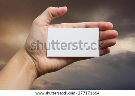 Hands holding a white business visit card, gift, ticket, pass, present closeup on sky background. Copy space.