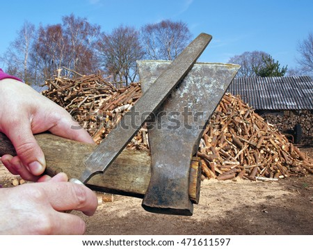 Hands holding an axe and sharpening by file on firewood log stack background.