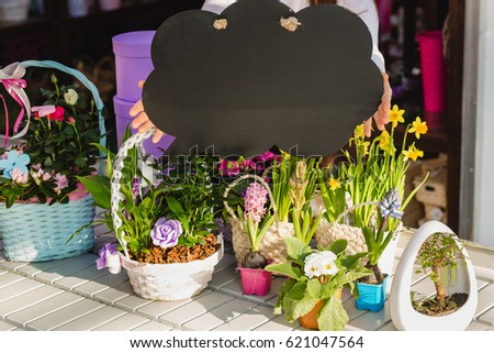Hands holding an empty speech cloud, above the counter with flowers.
