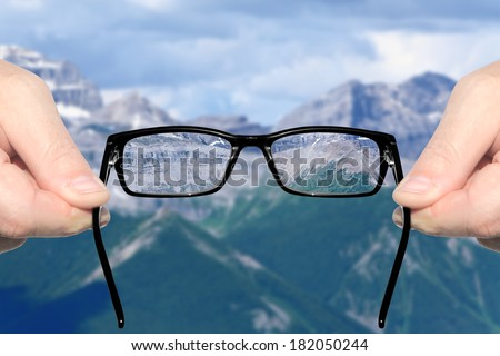Hands holding and offering eye glasses to look at amazing mountain landscape. Sharp as a good sight symbol and unsharp as a bad sight symbol  - stock photo