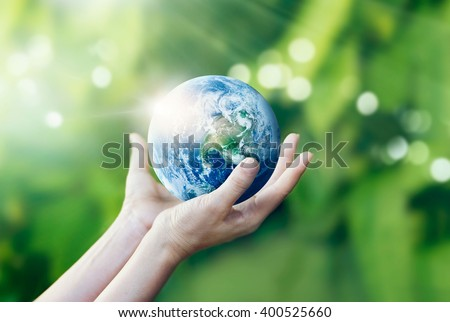 Hands holding and protect earth on nature background, Elements of this image furnished by NASA - stock photo