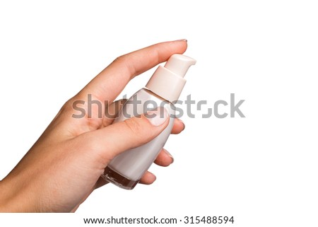 Hands holding and squeezing tube of cream