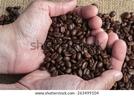 Hands holding Arabica coffee beans in shape of a heart, jute bag in background - stock photo