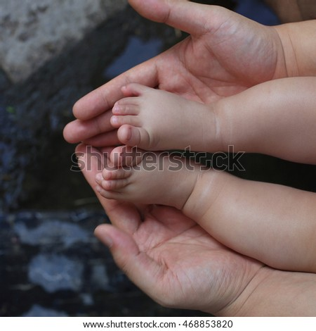 hands holding baby feet and legs