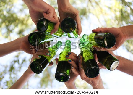 Hands holding beer bottles, close up - stock photo